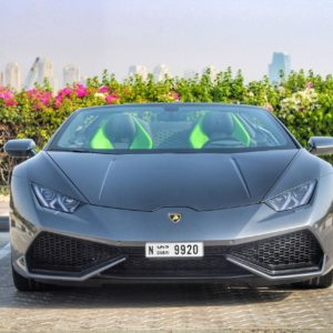 frontal view of silver lamborghini huracan spyder with skyline